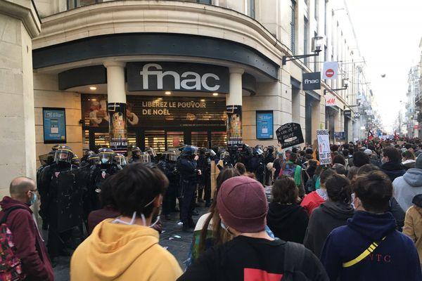 Les manifestants passent devant la Fnac protégée par les forces de l'ordre après avoir été vandalisée.