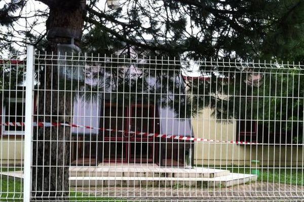 Derrière ces palissades on devine le cordon de sécurité mis en place autour de l'établissement