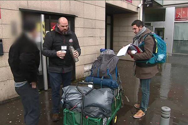 Deux bénévoles de l'Asar distribuent boisson chaude et nourriture à un homme sans abris à Rouen (Seine-Maritime).