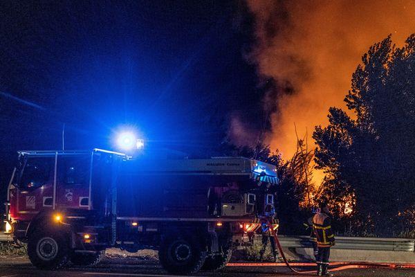 Un pompier armé d'une lance éteint un incendie - Photo d'illustration