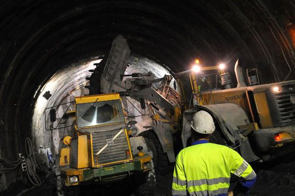Des engins travaillent sous le regard d'un ouvrier sur le chantier de la future ligne du TGV Lyon-Turin