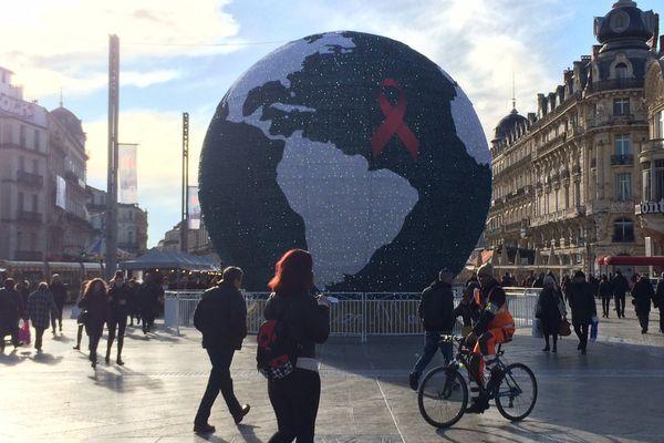 Un ruban a été déposé sur le globe de la place de la comédie, pour la journée mondiale de lutte contre le sida - 1er décembre 2017.