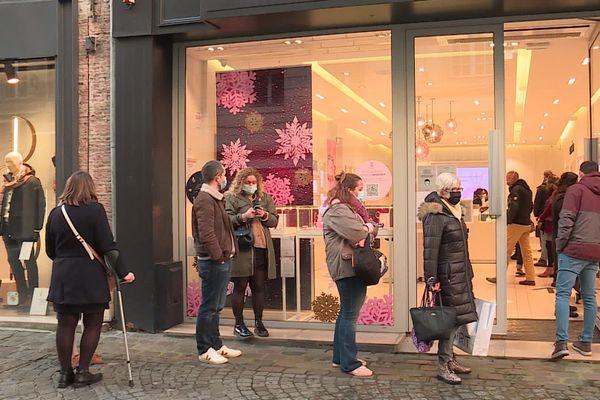Des clients font la queue devant un magasin.