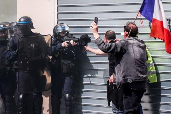 Un policier pointe son LBD en direction d'un gilet jaune, lors de la manifestation du 20 avril des gilets jaunes à Paris (illustration).