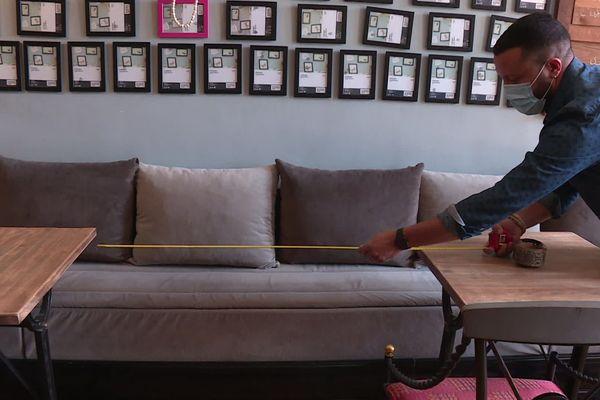 Un restaurateur mesure la distance entre deux tables de son restaurant