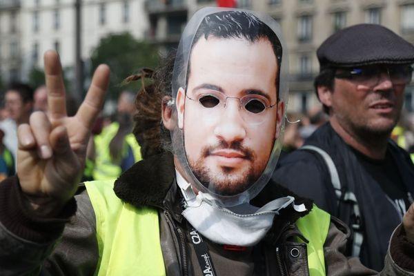 Un manifestant défile avec un masque reprenant le visage d'Alexandre Benalla, en marge du cortège intersyndical du 1er-Mai à Paris.
