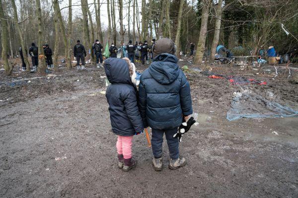 Deux enfants regardent les forces de l'ordre évacuer leur campement, à Grande-Synthe, en janvier 2021.