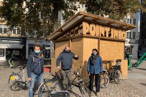"""L'équipe du festival devant le """"point info"""" de Scènes de rue installé place de la Réunion. Il ouvrira samedi 17 octobre à 11h."""