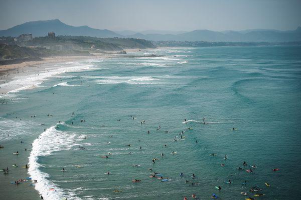 """Des surfers attendent la vague sur la plage de la Côte des Basques, en août 2018. Elle fait partie des quatorze nouvelles plages labellisées """"Pavillon Bleu"""", dans les Pyrénées-Atlantiques."""