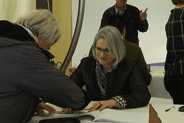 Une assesseure accueille un électeur