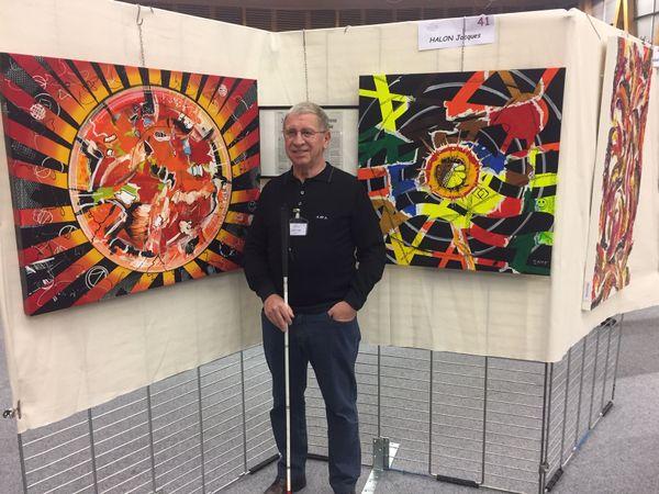 Jacques Halon, peintre aveugle devant deux de ses œuvres récentes