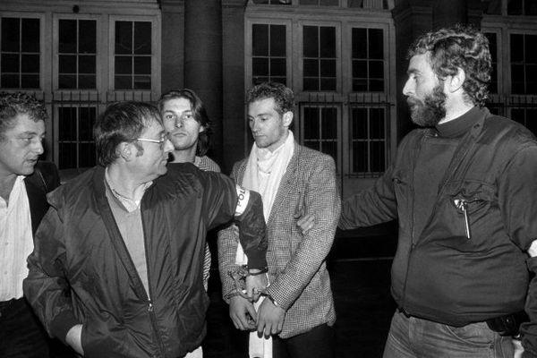 Lionel Cardon à son arrivée au 36, quai des Orfèvres entre deux policiers le 24 novembre 1983 après sa reddition.