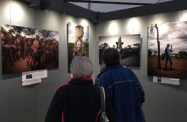 Des spectateurs devant l'exposition de l'Américain Scott Davies, consacrée aux populations humaines (ici les himba de Namibie et les mursi d'Éthiopie) dont l'habitat et les traditions sont menacées.