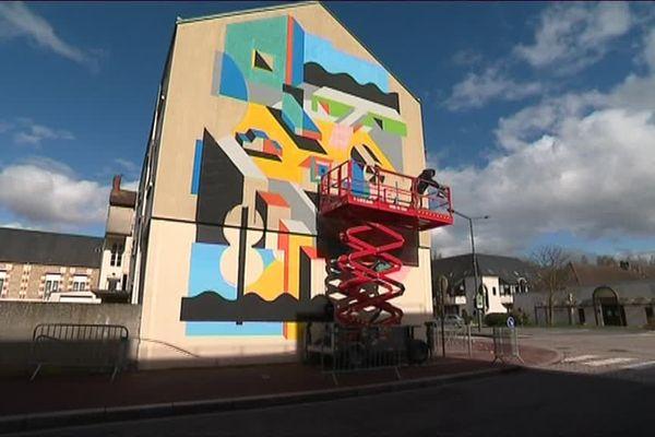 L'artiste hollandais Johann Moorman à l'oeuvre sur une façade de la rue Chapron à Mondeville, lors du festival PALMA 2018.