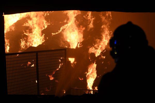 Un sapeur-pompier intervient sur un violent incendie dans un hangar agricole. Photo d'illustration.