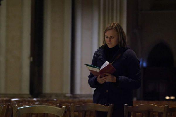 Marie-Hélène en train de prier debout avec un livre ouvert dans la Cathédrale de Chartres en Eure-et-Loir
