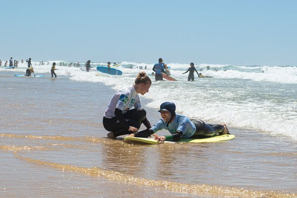 Une bénévole apprend le surf à un non-voyant sur la plage de Lacanau, avec l'association See Surf ( 5 juillet 2021)