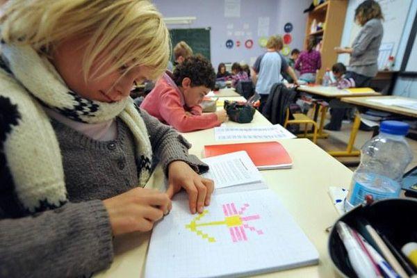 Un élève de CE1 dessine en classe