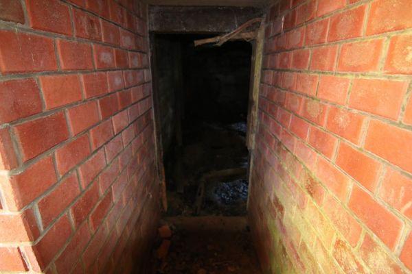 Un couloir en briques pour accéder à la pièce central du bunker.