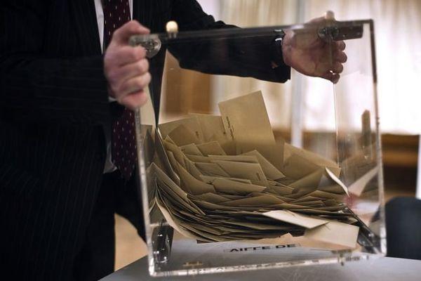 Un scrutateur vide l'urne contenant les bulletins de vote