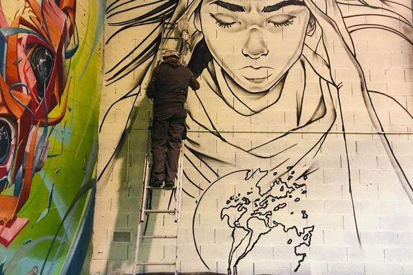 Snake en train de dessiner à la bombe une oeuvre pour l'association Cisart qui a ouvert un lieu dédié à Blagnac. Ce dessin dénonce le réchauffement climatique à travers une femme qui a mal en pensant à l'état du monde. Snake travaille des thématiques actuelles et n'oublie jamais ses valeurs lorsqu'il dessine.