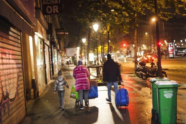 Une famille sans-abri marche dans la nuit à Paris, boulevard de Magenta (illustration).