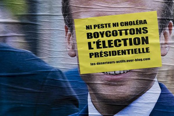 Un message appelant au boycott de l'élection présidentielle recouvre le visage d'Emmanuel Macron sur une affiche de campagne, à Paris, le 23 mars 2017.