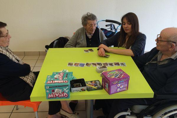 Les résidents de l'EHPAD de Culhat découvrent de nouveaux jeux de société avec Marion Daumas, animatrice de la médiathèque de Lezoux.