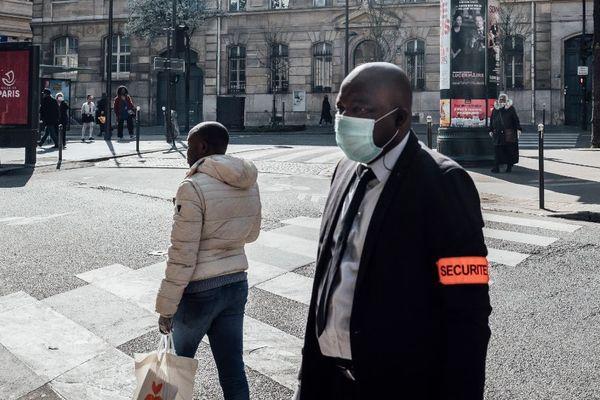 Un agent de sécurité devant un supermarché à Paris.