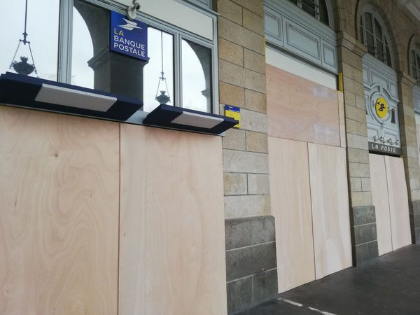 La Poste République sous les arcades protégée par des planches de contreplaqué
