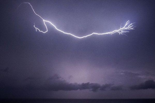 ILLUSTRATION - Un éclair déchire le ciel au dessus de la mer