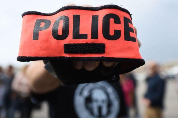 """Un policier brandit son brassard """"Police"""" lors d'une manifestation sur le Vieux-Port à Marseille, en octobre 2016."""