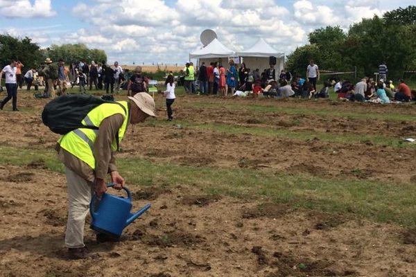 Un manifestant plante des semis sur un champ où doit s'installer le projet Europacity