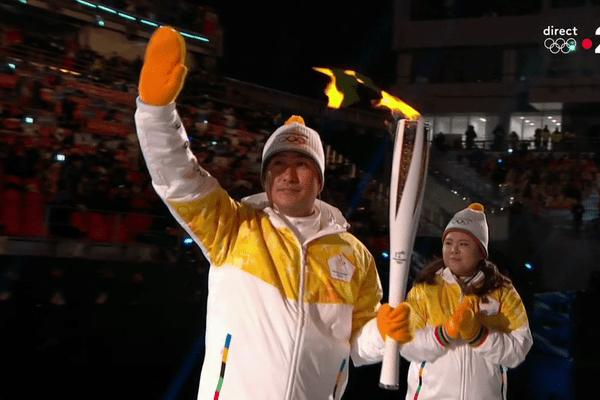 Le footballeur coréen Ahn Jung-hwan recevant la Flamme Olympique à Peyongchang, vendredi 9 février 2018, lors de la cérémonie d'ouverture des 23e jeux Olympiques d'hiver.