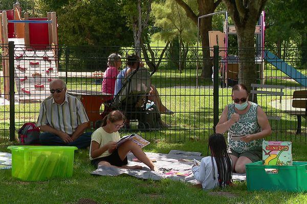 Jeux et livres sont proposés aux familles qui passent l'après-midi au plan d'eau du Bernouët à Saint-Jean-d'Angély (Charente-Maritime).