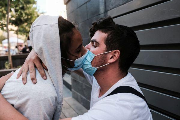 Un jeune couple s'embrasse avec un masque de protection