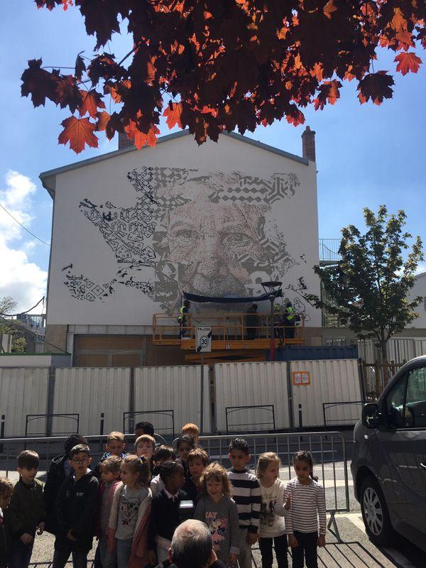 Les enfants de l'école Emile Gallé posent devant la fresque de l'artiste qu'ils ont rencontré.