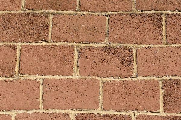 Sur le gros plan de ce mur, on distingue le matériau typique d'après-guerre: le parpaing de reconstruction, obtenu avec les gravats concassés des habitations bombardées.