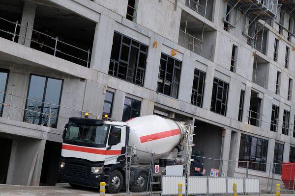 Camion livrant du béton sur un chantier de construction d'un immeuble.