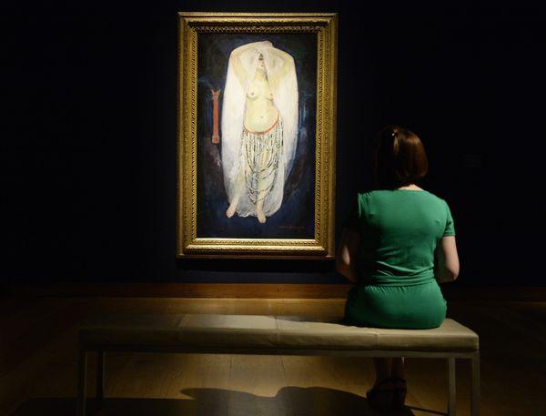 """Une employée de Christie's est assise devant le tableau de l'artiste français Kees Van Dongen's """"'Anita en Almée"""""""