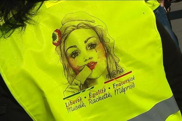Gilet jaune porté par une femme et ornant une Marianne en souffrance avec les mots : Muselé, Racketté, Méprisé.