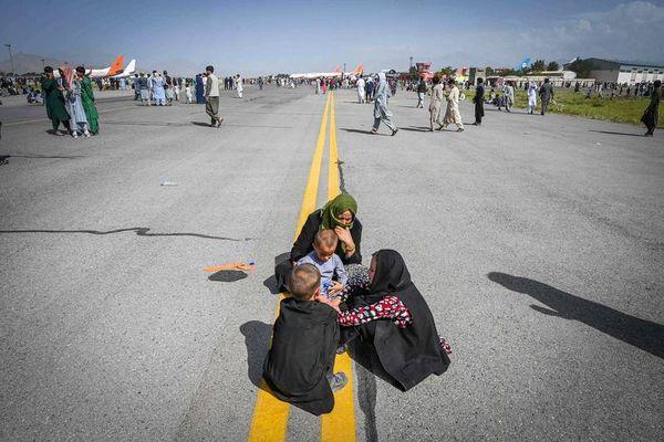 Des Afghans tentent de fuir le pays en attendant sur le tarmac de l'aéroport de Kaboul, lundi.