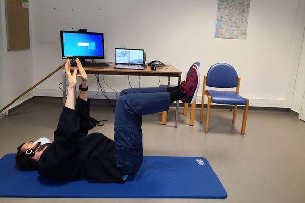 Vincent, kinésithérapeute en séance à distance avec Nathalie à laquelle il montre des mouvements