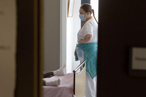 Une femme Agent de service hospitalier equipée de matériel de protection aide dans sa chambre une résidente d un EHPAD proche de Montpellier qui a été placée en isolement lié a l'épidemie de coronavirus.
