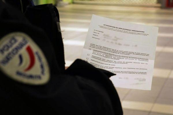 Un policier à Lille contrôlant une attestation de déplacement dérogatoire.
