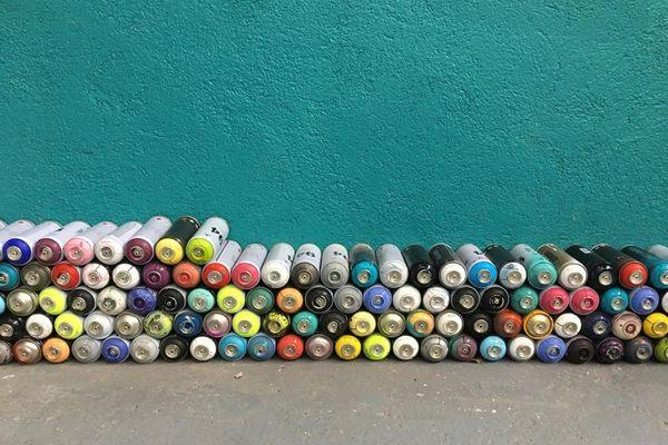 Outils artistiques : les bombes de peinture aérosol multicolores.