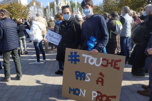 """""""#JeSuisProf"""", ou encore """"#TouchePasAMonProf"""" peut-on lire sur les pancartes des dijonnais rassemblés place de la République, ce dimanche 18 octobre."""