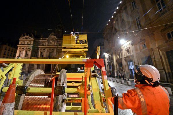 """Lyon, place des Terreaux, intervention des """"lignards"""" sur les câbles des lignes de trolleybus, un métier très technique pour renouveler des câbles alimentés à 700 volts"""