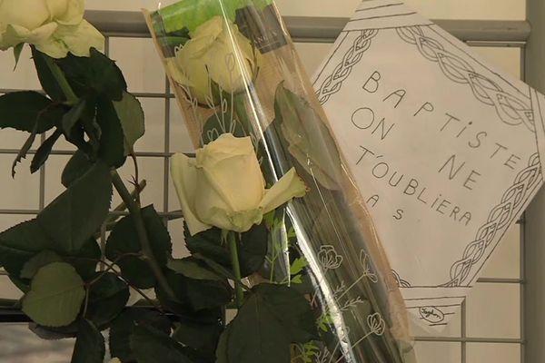 Sous un grand chapiteau blanc, devant l'établissement scolaire, des fleurs et des mots, en hommage à Baptiste