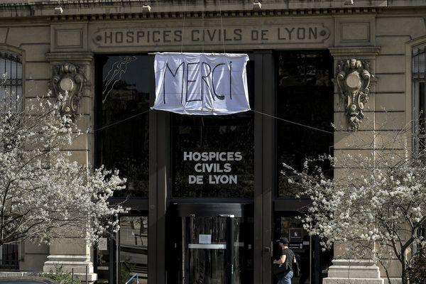 """Un drap blanc sur lequel est inscrit le mot """"merci"""" est attaché sur la façade du siège social des Hospices Civils de Lyon (HCL) au troisième jour de confinement en raison de la pandémie de Coronavirus Covid-19."""